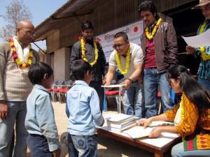 2_Treasurer handing educational materials to a student of Shree Kalika Primary School