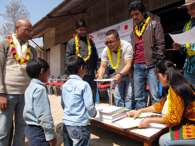 2_Treasurer handing educational materials to a student of Shree Kalika Primary School