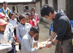 4_Member Takahiro Yazaki distributing educational materials to a student at Shree Raktakali Primary School