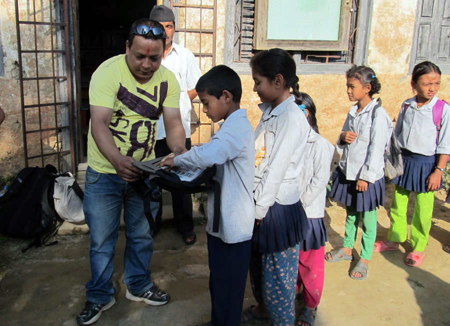 4_PEN Treasurer Bal Gopal Shrestha distributing carrying bags and stationery to students of Shree Raktkali Primary School
