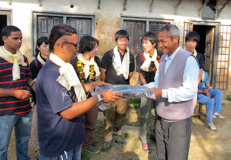 6_PEN Well wisher Akira Sahukhal handing over a bag to a teacher of Shree Raktkali