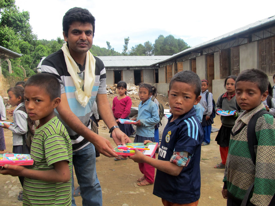 9_Secretary Binod P. Mainali handing over educational materials to the students of Shree Raktakali Primary School