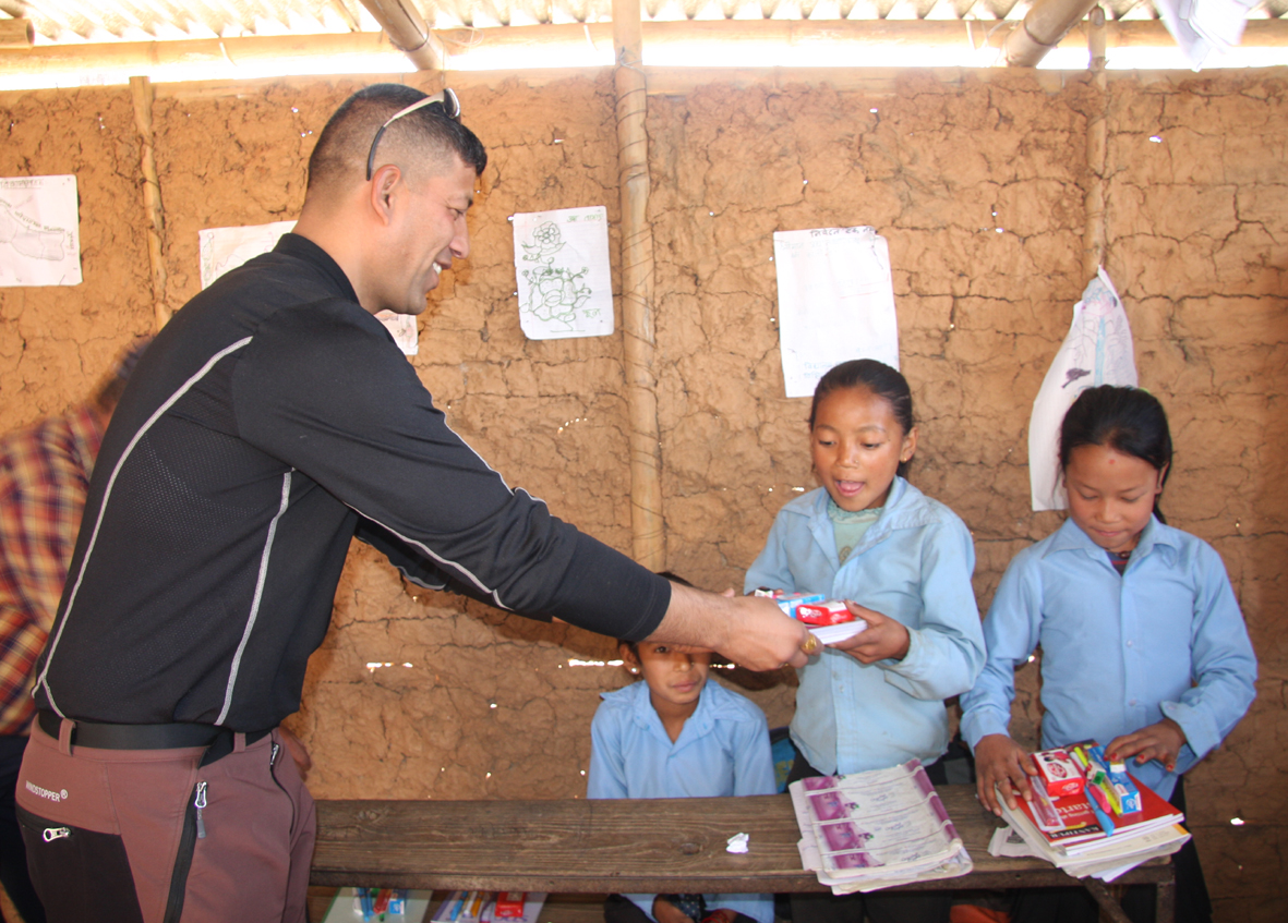 1_Member Kapil Deuja distributing educational and hygienic materials to a student of Seti Devi School