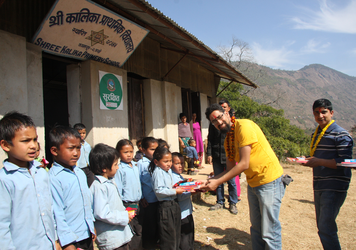 5_Coordinator Guna Raj distributing educational and hygienic materials to a student at Kalika school