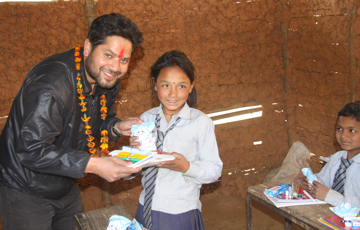 9_President Sujan Koirala distributing educational and hygienic materials to a student at Raktakali School