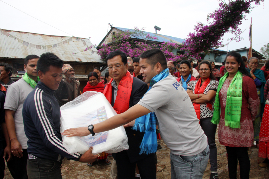 The World Bank Nepal Country office Sr. Operations Officer Bigyan Pradhan and Pax Earth Nepal President Sujan Koirala jointly distributing a Silpaulin sheet to a farmer in Kot Timal  village.