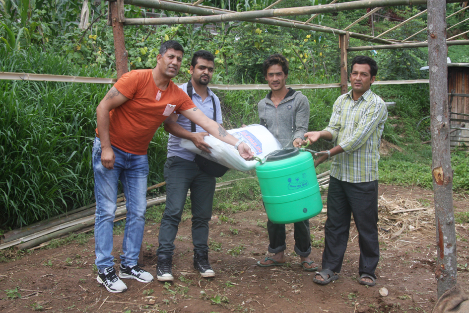 Pax Earth Members Kapil Deuja and Sital Mainali distributing a drip irrigation kit and a Silpaulin sheer to a farmer in Kot Timal village.